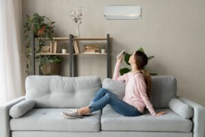 woman-using-remote-to-turn-on-ductless-air-handler-in-living-room